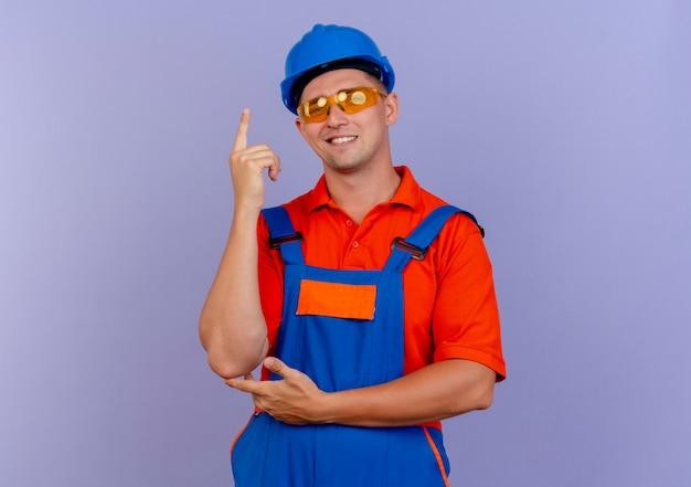 Der lächelnde junge männliche baumeister, der uniform und schutzhelm und schutzbrille trägt, zeigt nach oben