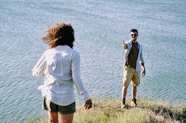 Der lächelnde junge männliche wanderer streckt seiner frau den arm entgegen und lädt sie ein, näher zu kommen und an einem sonnigen tag einen herrlichen blick auf den see zu genießen