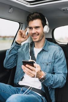 Der lächelnde junge mann, der die musik auf dem kopfhörer genießt, befestigt zum mobiltelefon