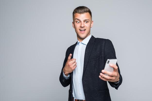 Der lächelnde junge mann hat einen videoanruf auf einem telefon, das in der dunklen jacke im studio auf grauer wand isoliert gekleidet ist
