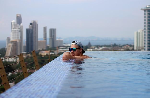 Der lächelnde junge mann mit mütze und brille genießt die aussicht vom pool auf dem dach am wolkenkratzer.