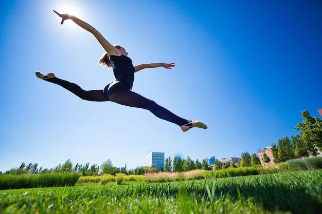 Der lächelnde junge turner springt gespalten und schwebt über der erde.