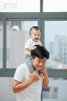 Der lächelnde junge vietnamesische vater reitet sein süßes kleines baby huckepack, wenn er wegen einer coronavirus-pandemie zu hause ist