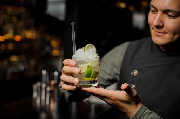Der lächelnde kellner, der ein glas hält, füllte mit caipirinha-cocktail mit einem strohhalm