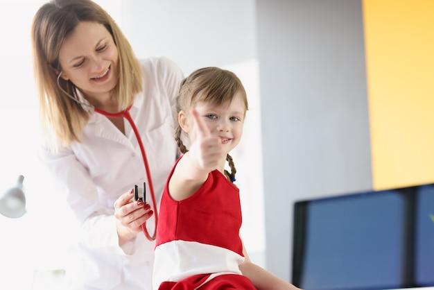 Der lächelnde kinderarzt hört durch das stethoskop auf die atmung der lunge von
