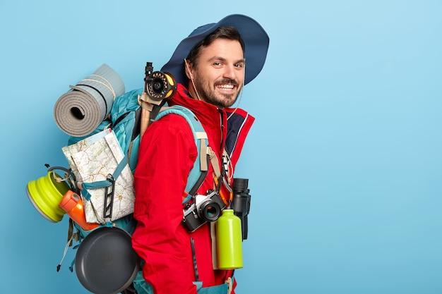 Der lächelnde männliche tourist trägt hut und rote jacke, trägt einen rucksack mit karte, karemat, benutzt ein fernglas, eine flasche mit heißem getränk