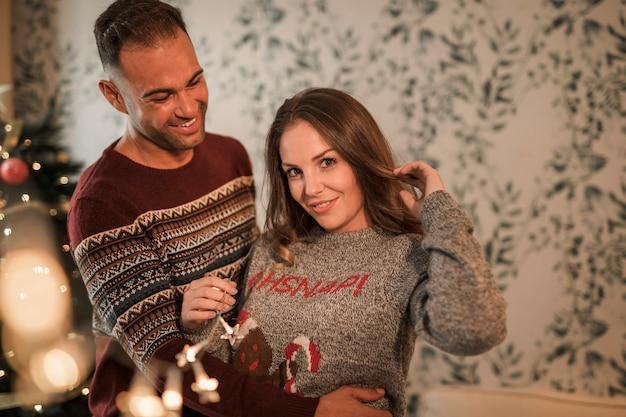 Der lächelnde mann, der nette frau in den strickjacken umarmt, nähern sich weihnachtsbaum