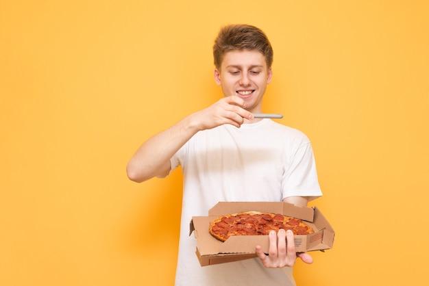Der lächelnde mann hält eine schachtel frische pizza in der hand und macht ein foto auf einem smartphone