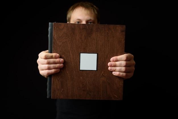 Der lächelnde mann hält fotobücher in einer holzhülle