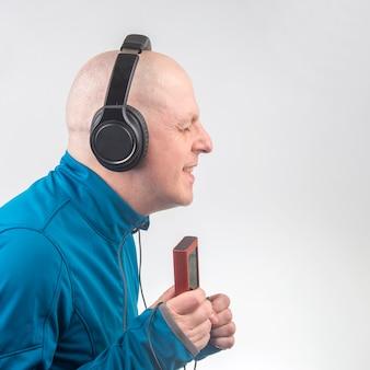 Der lächelnde mann mit kopfhörern und digitalem tragbarem player in der hand entspannt sich, während er seine lieblingsmusik hört