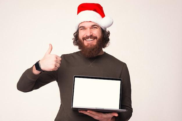 Der lächelnde mann mit weihnachtsmütze zeigt daumen nach oben und hält seinen laptop mit angezeigtem bildschirm.