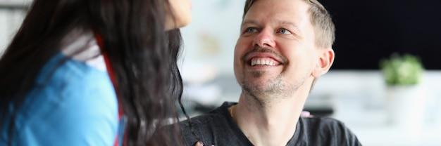 Der lächelnde mann sieht die doktorfrau mit zuversicht an. wiederherstellungsfähigkeit menschen mit behinderungen zu haushaltsbezogenen, sozialen aktivitäten. rehabilitation in der klinik. wiederherstellung und anpassung an das leben nach einem unfall