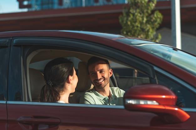 Der lächelnde mann und die frau, die im auto sitzen