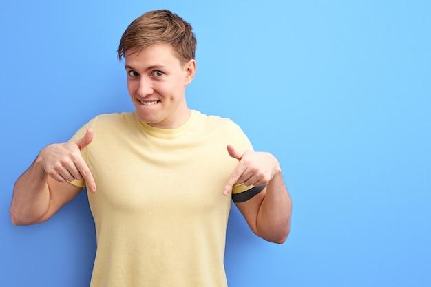 Der lächelnde mann zeigt mit dem zeigefinger nach unten und zeigt etwas, das werbekonzept. menschen aufrichtige emotionen lifestyle-konzept. kopierraum nachahmen