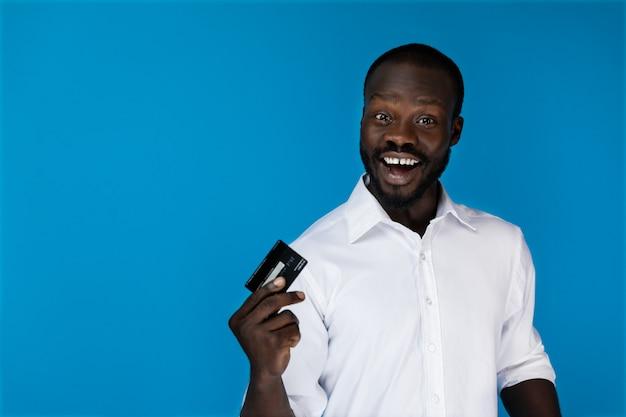 Der lächelnde schauende afroamerikanische mann im weißen hemd hält kreditkarte in einer hand