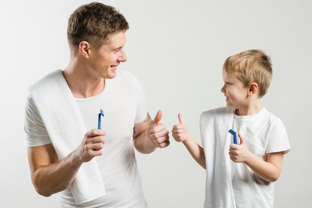 Der lächelnde vater und sohn, die in der hand das rasiermesser hält, zeigen daumen herauf zeichen auf weißem hintergrund gegen weißen hintergrund