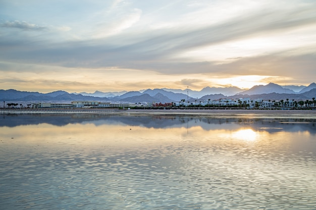 Der landschaftshimmel spiegelt sich im meer mit einsamen figuren in der ferne wider.