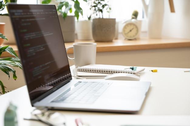 Der laptop auf einem weißen schreibtisch in einem hellen büro zeigt den code auf dem bildschirm an