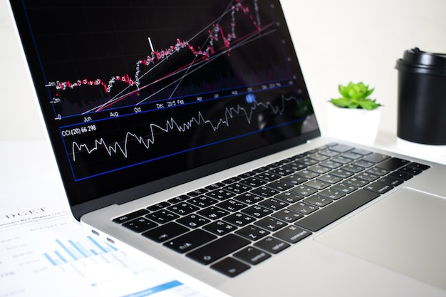 Der laptop-bildschirm zeigt finanzielle diagramme und grafiken im büro.