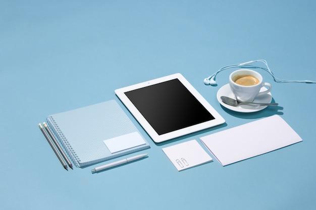 Der laptop, stifte, telefon, notiz mit leerem bildschirm auf dem tisch