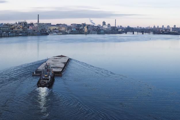 Der lastkahn schwimmt im dnepr. kiewer stadtlandschaft