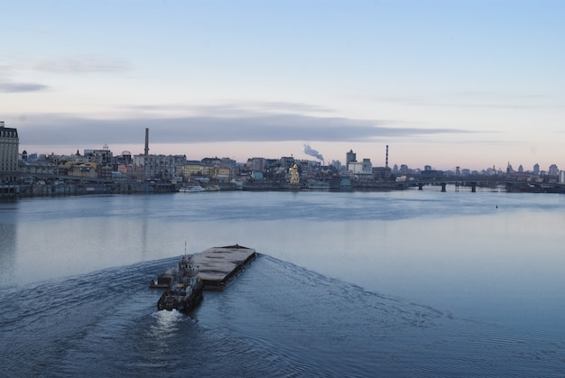 Der lastkahn schwimmt im dnepr. kyiv stadtlandschaft im hintergrund. 17.11.2018