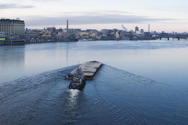 Der lastkahn schwimmt im dnepr. kyiv stadtlandschaft im hintergrund.