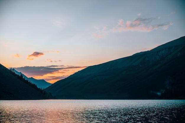 Der lebendige morgenhimmel spiegelt sich bei sonnenaufgang im reinen alpensee in der nähe von bergsilhouetten wider.