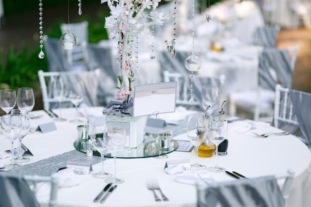 Der leere teller steht auf einem wunderschön servierten feiertagstisch, der mit einer weißen tischdecke bedeckt ist