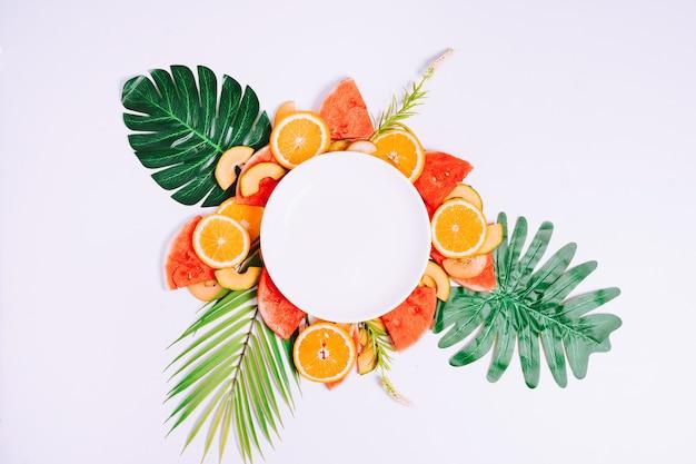 Der leere teller wird auf tropische fruchtstücke gelegt