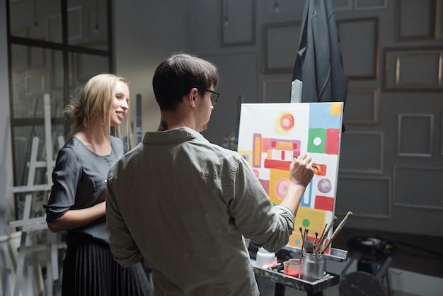 Der lehrer für malerei berät einen seiner schüler und hilft ihr mit einem unvollendeten bild auf leinwand vor der staffelei