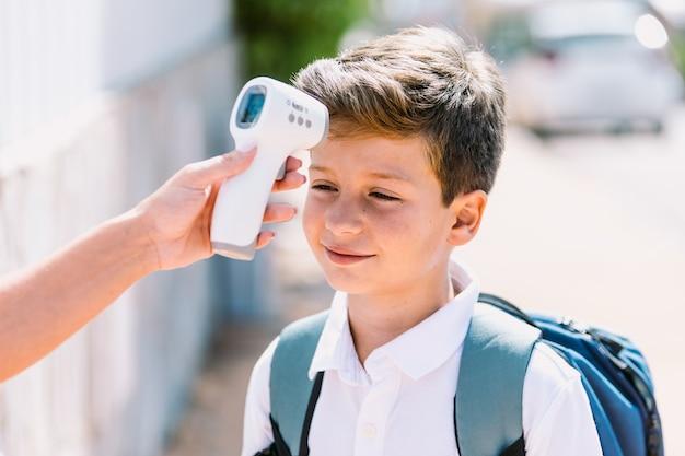 Der lehrer misst die temperatur eines kindes beim schuleintritt mit einem elektronischen thermometer. covid-19- und virus-pandemie-konzept