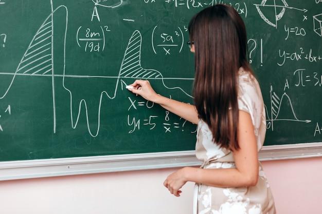 Der lehrer schreibt ein beispiel an die tafel und erklärt eine lektion.