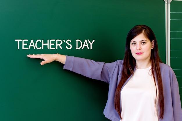 Der lehrer steht an der tafel und zeigt auf den tag der inschriftenlehrer