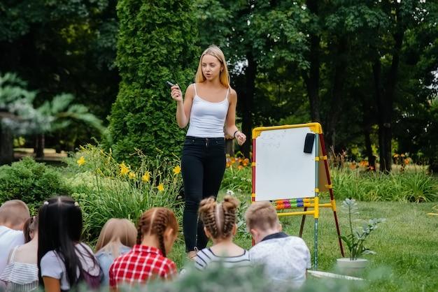 Der lehrer unterrichtet eine klasse von kindern in einem park im freien