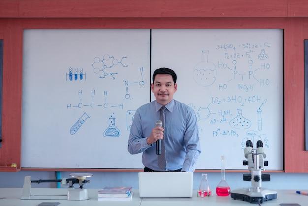 Der lehrer unterrichtet während der sperrung aufgrund der covid-19-pandemie online naturwissenschaften. konzept des glücklichen lehrertages