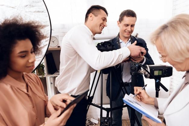 Der lehrer zeigt, wie man die kamera benutzt.
