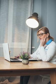 Der leitende arzt hat ein online-treffen mit den patienten über einen laptop im büro