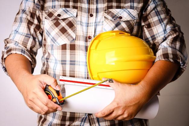 Der leiter der bauabteilung trägt ein kariertes hemd mit einem gelben schutzhelm und konstruktionspapier.