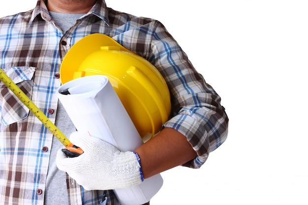 Der leiter der konstruktionsabteilung trägt ein kariertes hemd mit gelbem schutzhelm und konstruktionspapier.