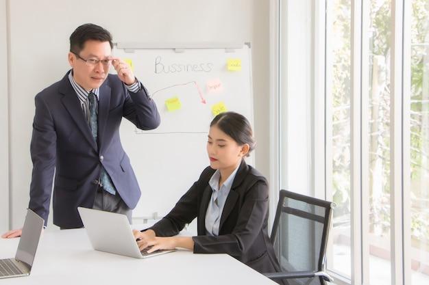 Der leiter und die sekretärin helfen bei der formulierung eines strategischen plans, der dem unternehmen hilft, das virusvirus am morgen im büro-besprechungsraum zu überleben.