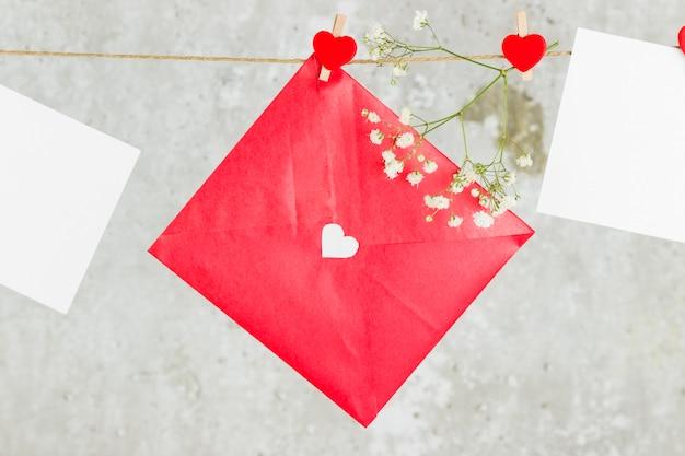 Der liebesbrief hängt am seil und einer blume auf hellem hintergrund.