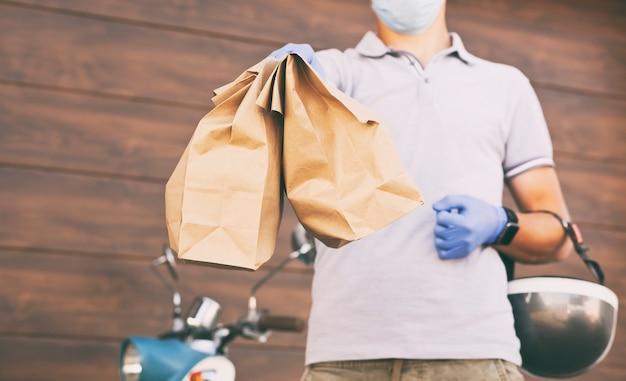 Der lieferbote liefert das essen mit seinem moped an den kunden