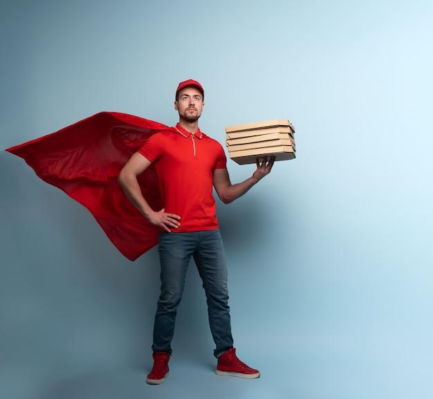 Der lieferbote mit pizza verhält sich wie ein mächtiger superheld. erfolgskonzept und versandgarantie. cyan hintergrund