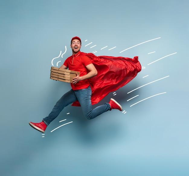 Der lieferbote mit pizza verhält sich wie ein mächtiger superheld. erfolgskonzept und versandgarantie. studio cyan hintergrund