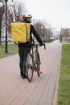 Der lieferbote trägt eine medizinische maske und einen thermo-rucksack und geht nach dem fahrradfahren in die stadt