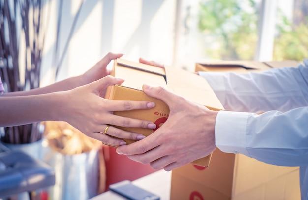 Der lieferer übergibt einer frau pakete