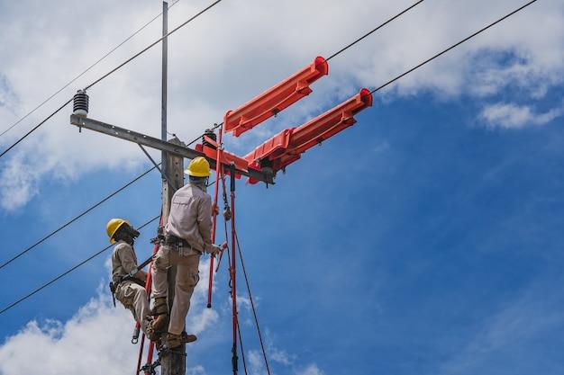 Der lineman schnitzte mit einem kabelbinder den kabelbinder, mit dem die elektrischen kabel umwickelt wurden