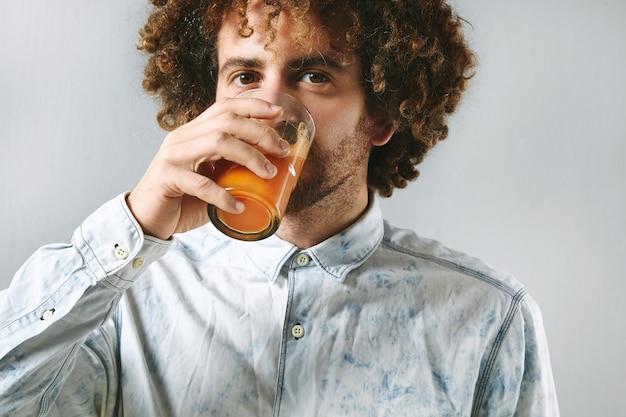 Der lockige junge bärtige mann im weißen jeanshemd trinkt frisch gepressten natürlichen saft von den bio-karotten des bauernhofs.