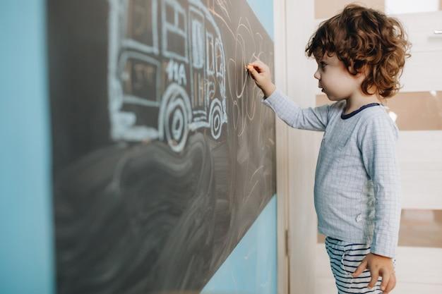 Der lockige kleine junge zeichnet kreide auf ein brett in seinem zimmer